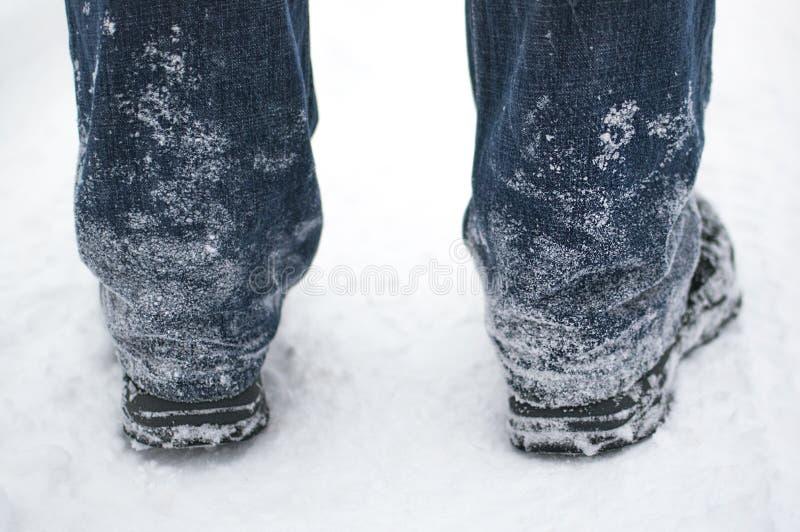 Bevroren sneeuw op jeans en zwarte laarzen van een mens in de winter, achtermening stock fotografie
