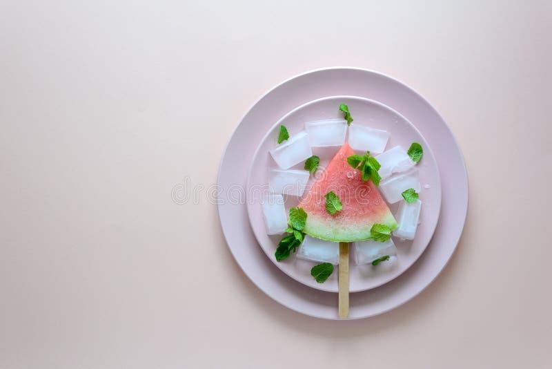 Bevroren watermeloenijslollys met munt op roze plaat stock foto's