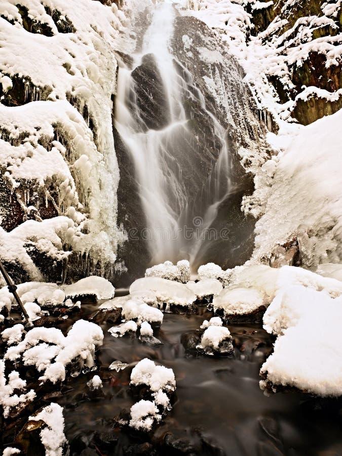 Bevroren waterval De winterkreek, ijzige stenen en takken stock afbeelding