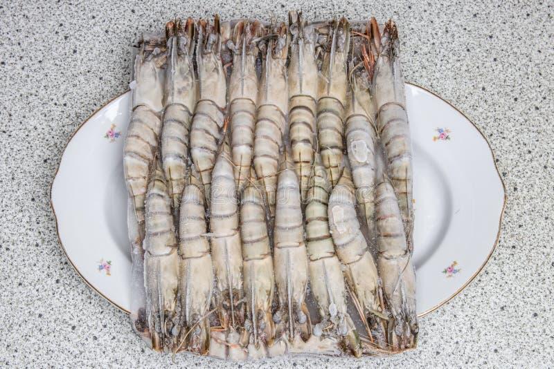 Bevroren zeevruchtenachtergrond Close-up van bevroren verse ruwe tijgergarnalen op een plaat Hoogste mening Concepten gezond voed royalty-vrije stock afbeelding
