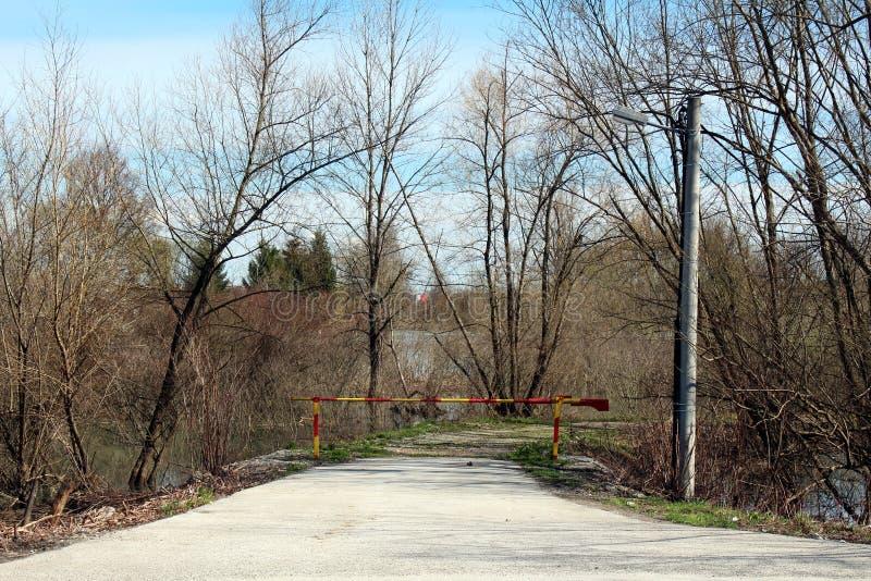 Bevuxen väg som omges fullständigt med stora träd utan sidor och det översvämmade fältet som stängs med rampen för röd och gul me arkivfoton