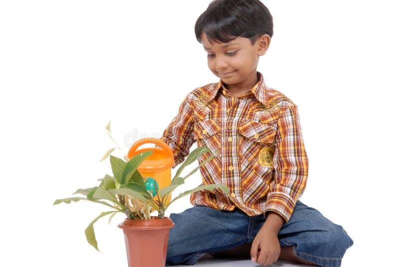 Bewässerungsanlage des kleinen Jungen des Gärtners stockbild