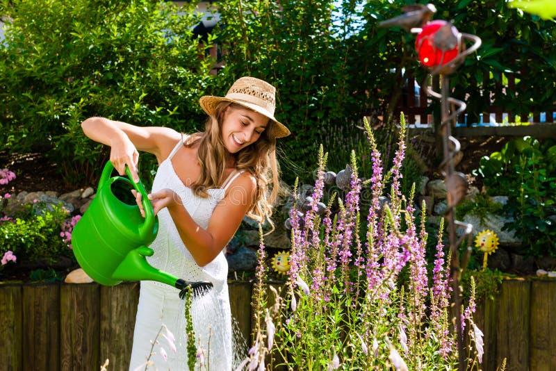 Bewässerungsblumen des Frauengärtners im Garten stockbilder