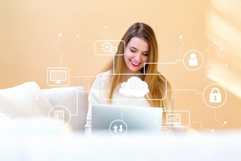 Bewölken Sie die Datenverarbeitung mit der jungen Frau, die ihren Laptop verwendet stockbild