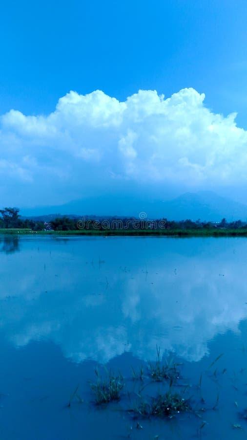 bewölkt Reflexion auf einem ruhigen See lizenzfreie stockfotos