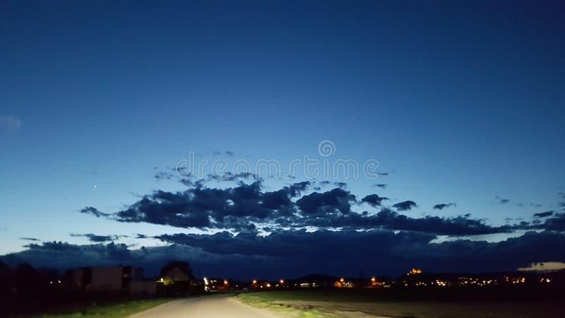 bewölkt schöner Abendhaupthimmel der Straße helle Scheinwerfer stockbilder