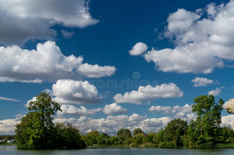 Bewölkter blauer Himmel über Grün und See lizenzfreie stockfotos