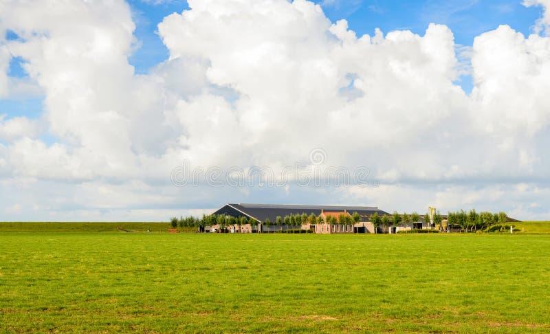 Bewölkter Himmel über einer niederländischen Polderlandschaft mit einem Bauernhof stockfotos
