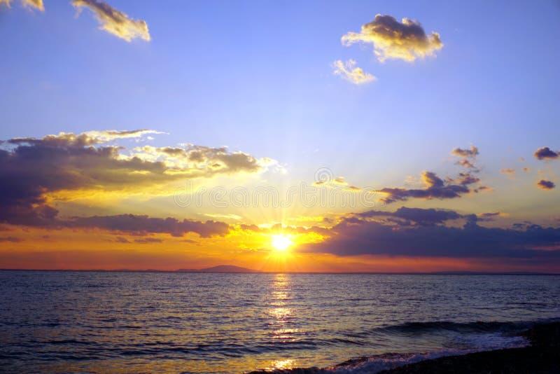 Bewölkter Himmel bei Sonnenuntergang an der Seeküste im klaren blauen, purpurroten, gelben und orange Farbton stockfotografie