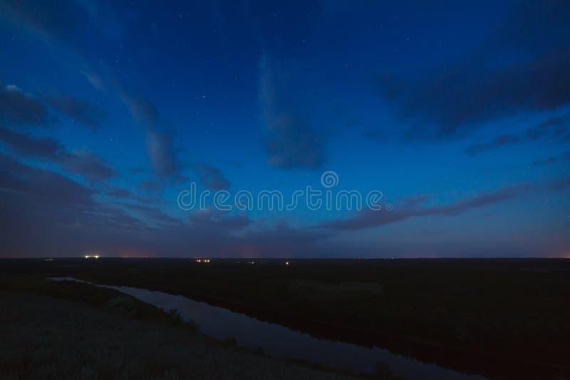 Bewölkter nächtlicher Himmel über Fluss vor Dämmerung lizenzfreies stockfoto