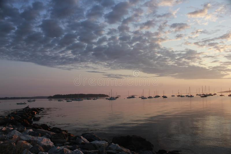 Bewölkter Sonnenaufgang über Casco-Bucht mit Booten im Hintergrund lizenzfreie stockfotos