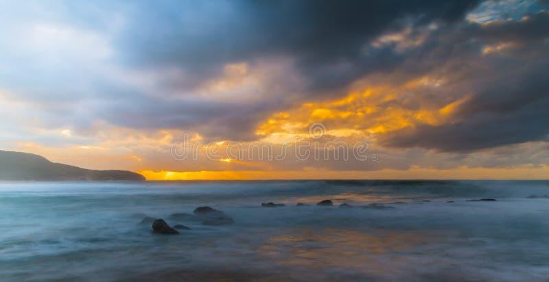 Bewölkter Sonnenaufgang-Meerblick mit einem Spritzen der Orange stockbild