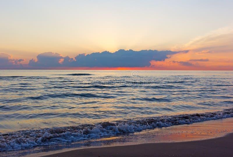 Bewölkter Sonnenaufgang und Meereswellen, die auf einem leeren sandigen Strand rollen stockbild