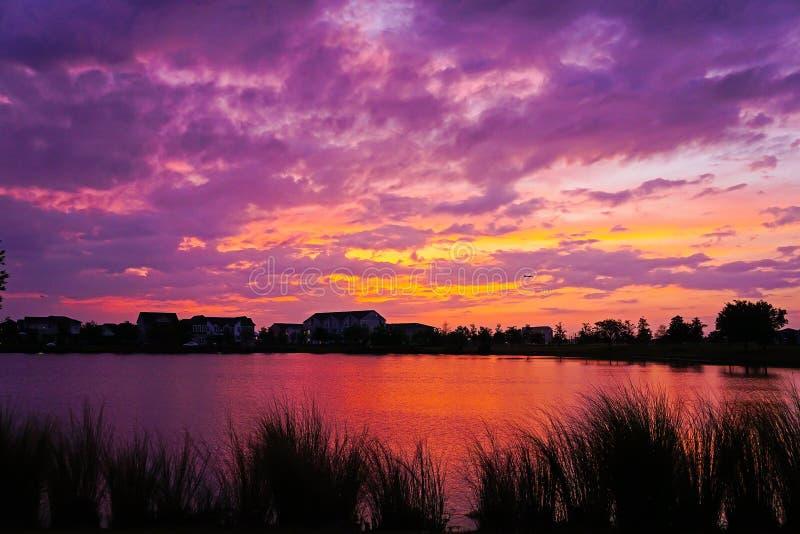 Bew?lkter Sonnenuntergang ?ber einem See stockfotografie
