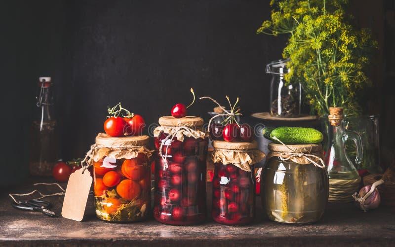 Bewaard en vergist voedsel in glaskruiken - groenten in het zuur, jam, compote met tomaten, komkommer en kersen op donkere rustie stock afbeelding