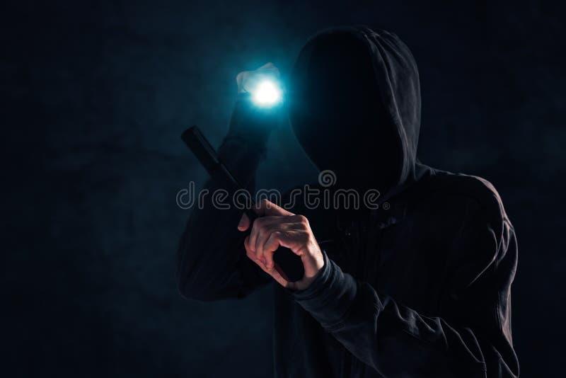 Bewaffneter Überfall, kriminell mit dem Gewehr und Fackel, die in der Dunkelheit angreifen stockfotografie
