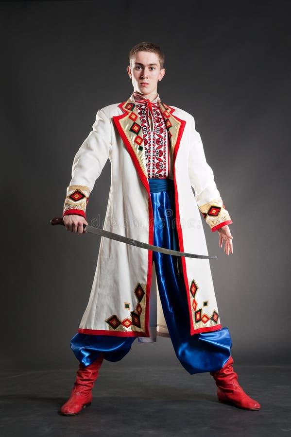 Bewaffneter junger Kosake im nationalen ukrainischen Kleid lizenzfreie stockfotos