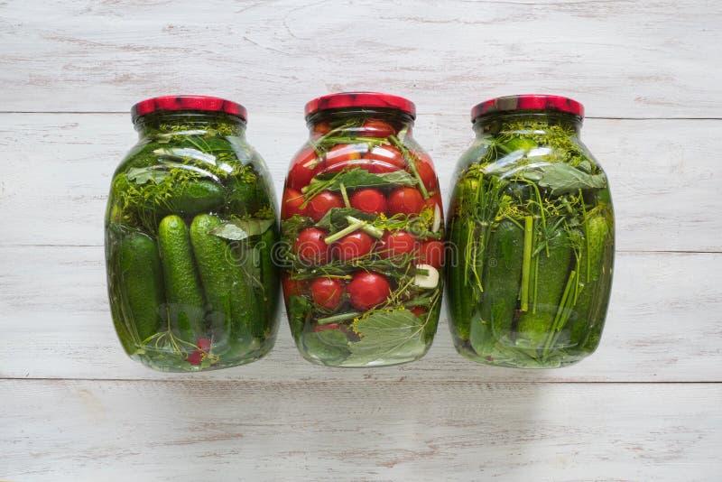 Bewahrung von Tomaten und von Gurken Gläser Essiggurken und Tomaten für den Winter stockbilder