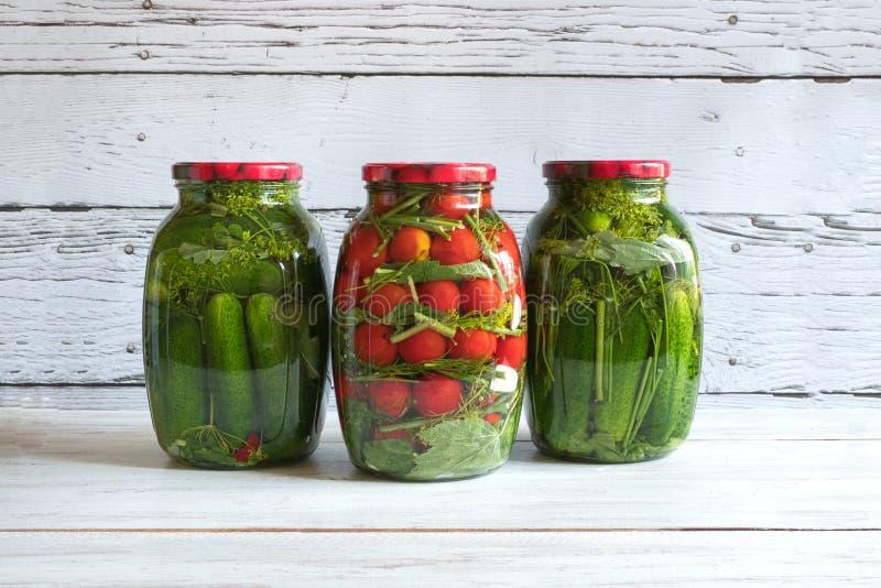 Bewahrung von Tomaten und von Gurken Gläser Essiggurken und Tomaten für den Winter lizenzfreies stockbild