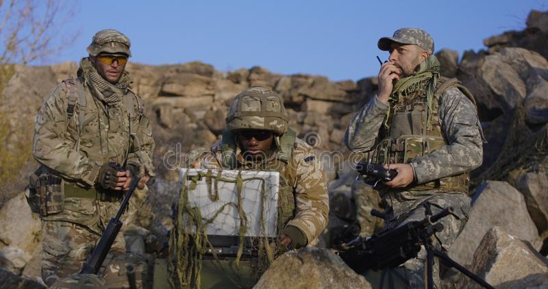 Bewapende Afrikaanse Amerikaanse militair die een computer bekijken stock foto