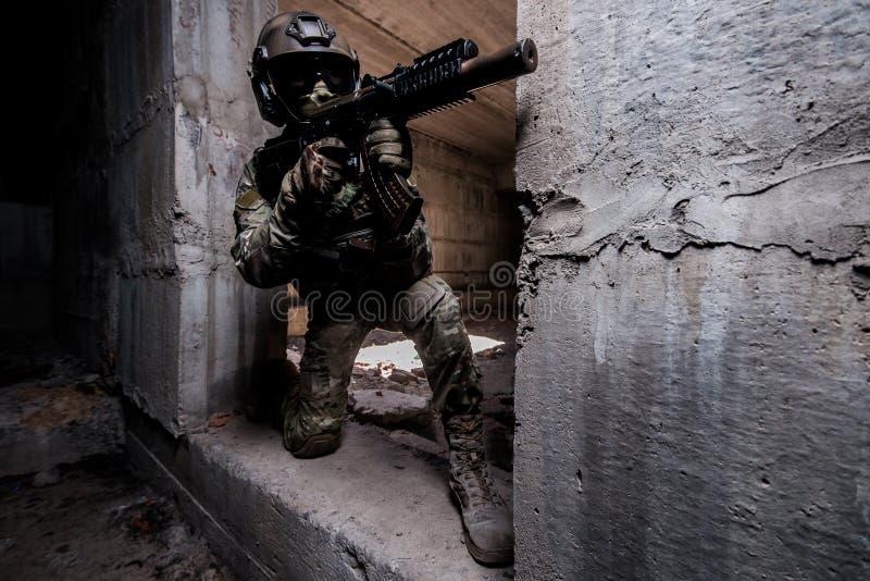 Bewapende boswachter binnen in masker en helm het verbergen in een gebouw stock foto's