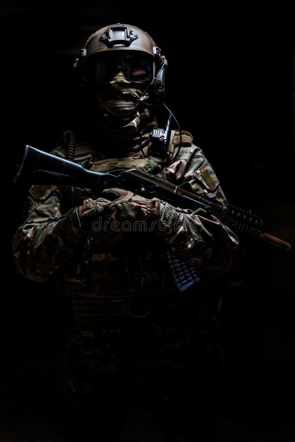 Bewapende boswachter in camouflage die en zich de camera bevinden bekijken stock fotografie