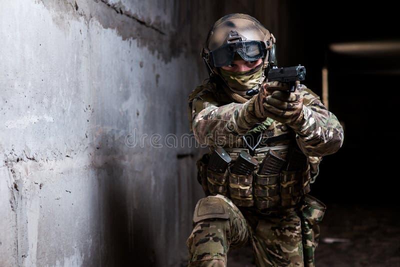 Bewapende boswachter die in camouflage zijn kanon in de donkere ruimte streven royalty-vrije stock foto's