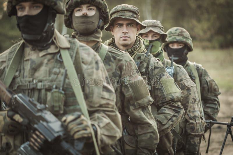 Bewapende jonge gemaskeerde militairen stock fotografie