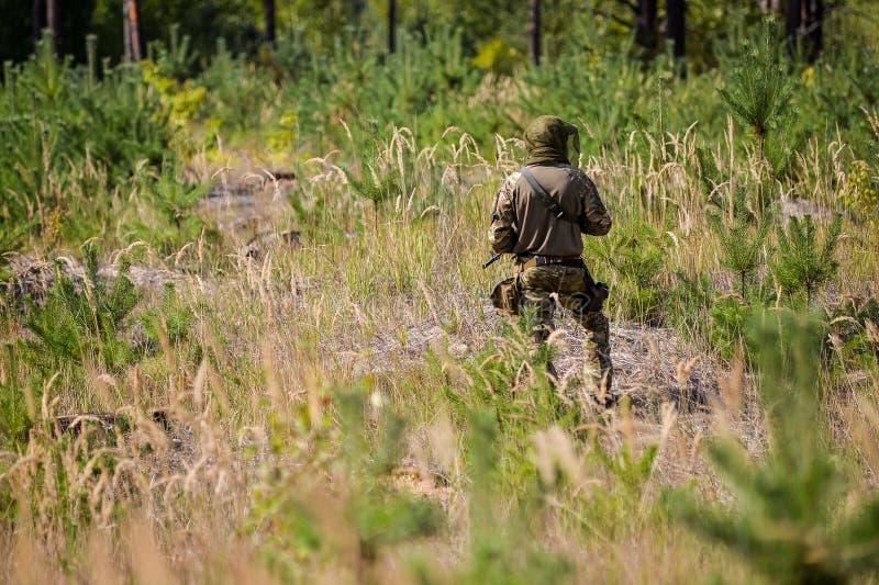 Bewapende militair in camouflage op patrouille op het gebied stock afbeeldingen