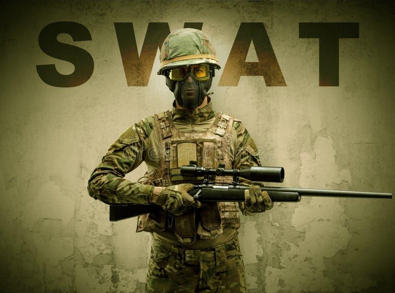 Bewapende militair met beschadigde muurachtergrond stock foto's