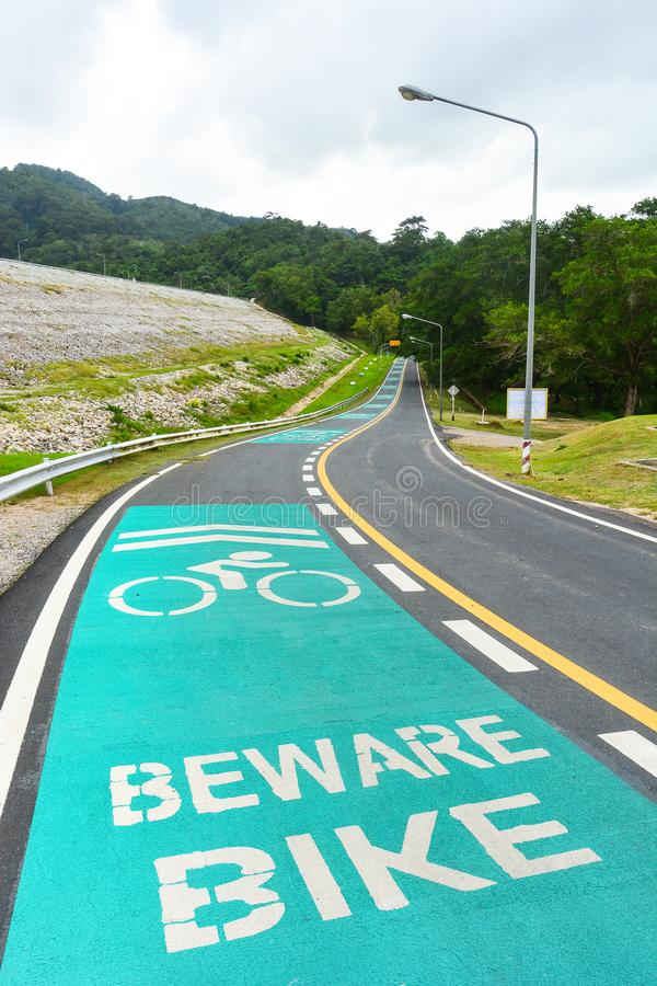 Beware bike sign painted on bike lane in public park stock photography