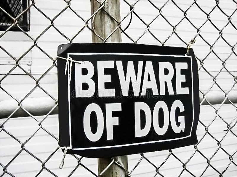 A beware of dog sign on a mesh fence as a safeguard warning of dangerous rottweiler attack if trespassing. Private, restricted property - Concept of burglar stock images