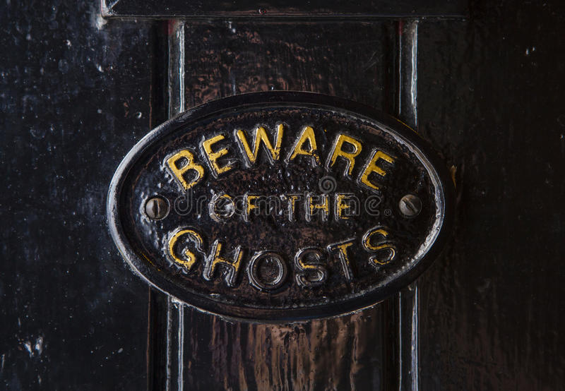 Beware of the Ghosts. A Beware of the Ghosts plaque on the entrance to the Golden Fleece public house in York, England. It is regarded to be the most haunted pub royalty free stock photography