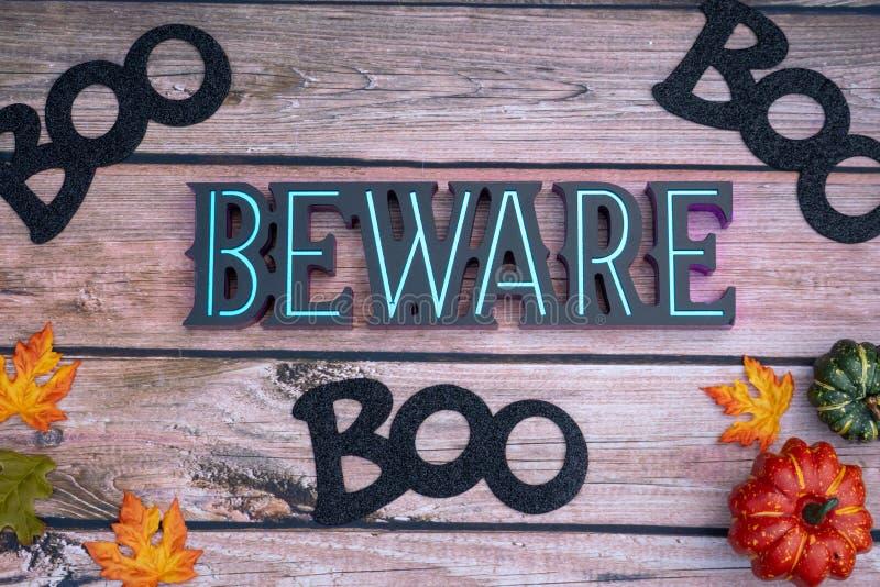 Beware huent le fond de Halloween sur le contexte en bois avec des potirons image stock