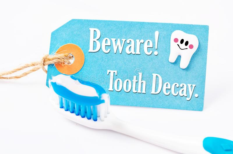 Beware tooth decay. Beware tooth decay with toothpaste and toothbrush royalty free stock photography