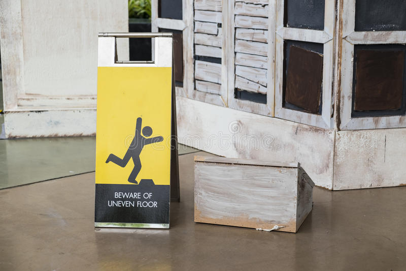 Beware uneven floor sign. In department store stock photography