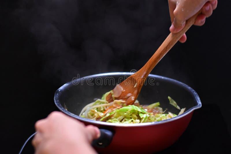 Beweeg Fried Mixed Vegetable in teflon panhittebron door inductio royalty-vrije stock foto's