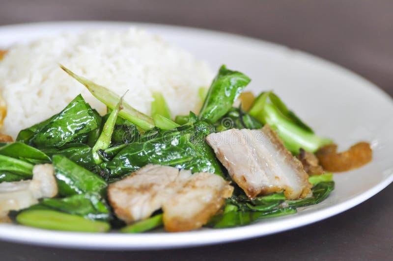 Beweeg gebraden boerenkool met knapperige varkensvlees en rijst royalty-vrije stock afbeelding