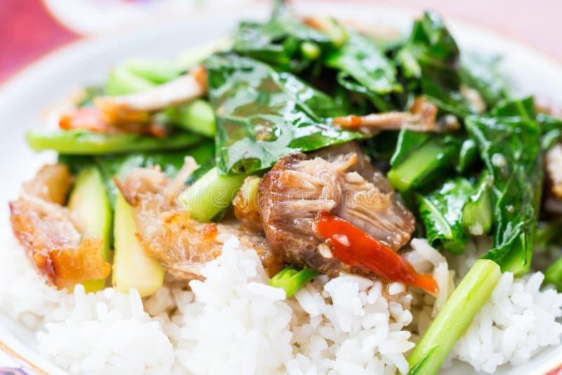 Beweeg gebraden boerenkool met knapperige varkensvlees en rijst royalty-vrije stock afbeeldingen