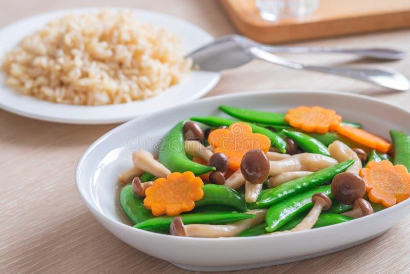 Beweeg gebraden gemengde groenten en ongepelde rijst, Vegetarisch voedsel stock afbeeldingen