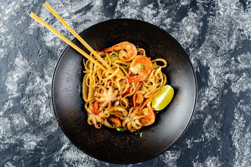 Beweeg gebraden gerechtnoedels met groenten en zeevruchten in zwarte kom royalty-vrije stock afbeelding