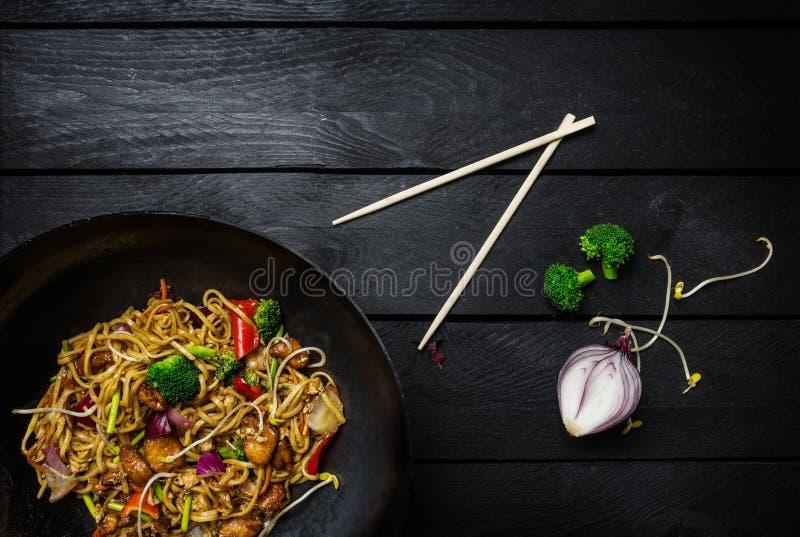 Beweeg gebraden gerechtnoedels in traditionele Chinese wok, eetstokjes en ingrediënten Ruimte voor tekst stock foto