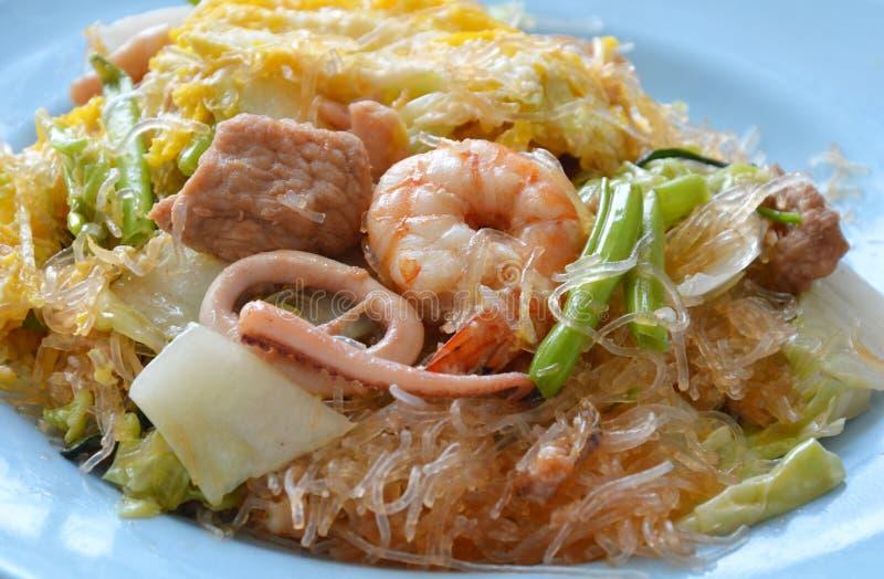 Beweeg gebraden sukiyaki met ei en zeevruchten op schotel stock afbeeldingen