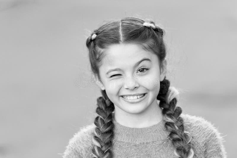 Beweer en gekscherend Speelse kind vrolijke uitdrukking Dingen die gaan in orde zijn Het meisje knipoogt vrolijke gezichts grijze stock foto's