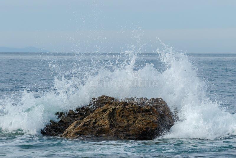 Bewegen Sie das Brechen auf Felsen gerade über Strand, Laguna Beach, Kalifornien hinaus wellenartig stockfotos