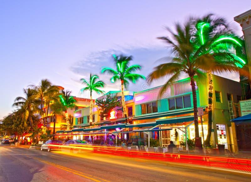 Bewegend verkeer, Verlichte hotels en restaurants bij zonsondergang op Oceaanaandrijving royalty-vrije stock fotografie