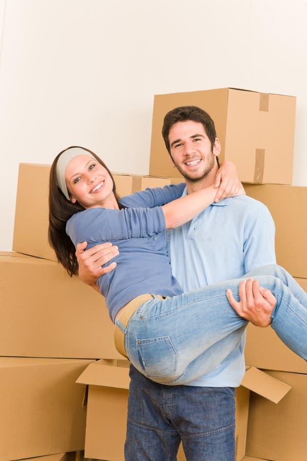 Bewegende nieuwe huis jonge man holdingsvrouw stock afbeelding