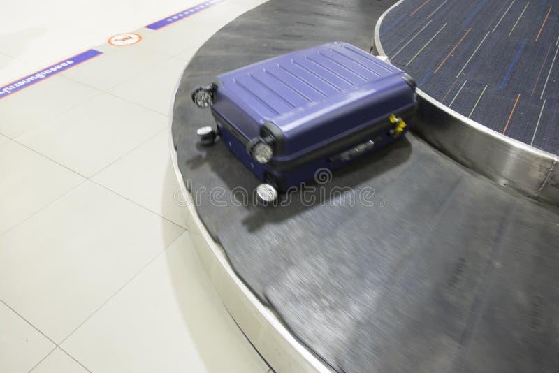 Beweging van blauwe zak op transportband in de luchthaven stock afbeeldingen