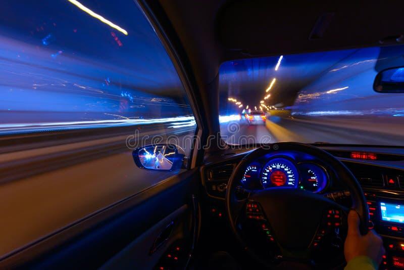 Beweging van de auto bij nacht op de weg van het land bij een hoge snelheid van het bekijken van de binnenkant met de bestuurder  royalty-vrije stock afbeeldingen