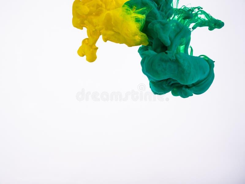 Beweging van gele en groene acryldruppeltjes in vloeistof Twee druppeltjes van kleurrijke inkt in water, een abstracte banner royalty-vrije stock afbeelding